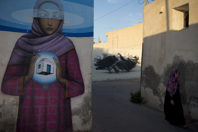 """A woman walks past murals by French artist SETH in the village of Erriadh, on the Tunisian island of Djerba, on August 7, 2014, as part of the artistic project """"Djerbahood"""". (Photo by Joel Saget/AFP Photo)"""