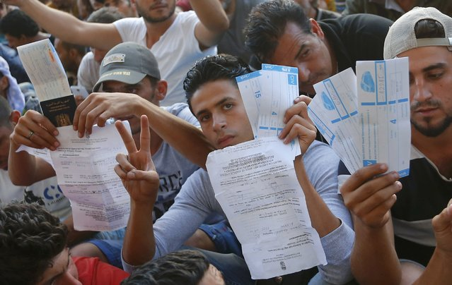 Refugees raise their documents and railways tickets outside the Keleti station in Budapest, Hungary September 2, 2015. (Photo by Laszlo Balogh/Reuters)