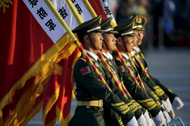 Paramilitary policemen carrying flags prepare in front of the Tiananmen Gate ahead of the military parade to mark the 70th anniversary of the end of World War Two, in Beijing, China, September 3, 2015. (Photo by Jason Lee/Reuters)