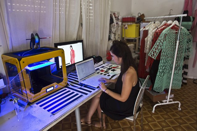 Israeli fashion design student from the Shenkar College of Engineering and Design Danit Peleg works on her laptop beside a 3-D printing machine at her home-based studio in Tel Aviv, Israel August 31, 2015. (Photo by Nir Elias/Reuters)