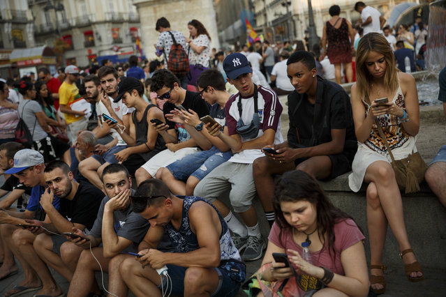 Spanish fans play the addictive Pokemon Go game during a gathering in central Madrid, Spain, Thursday, July 28, 2016, to play the computer game. In the game players try to capture, battle, and train virtual creatures in their real world locations using the GPS and camera on their smart devices. (Photo by Daniel Ochoa de Olza/AP Photo)