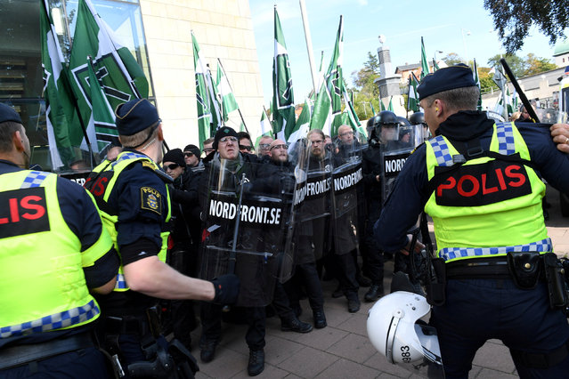Police officers stop NMR demonstrators from trying to walk along a forbidden street during the Nordic Resistance Movement (NMR) march in central Gothenburg, Sweden September 30, 2017. (Photo by Fredrik Sandberg/Reuters/TT News Agency)