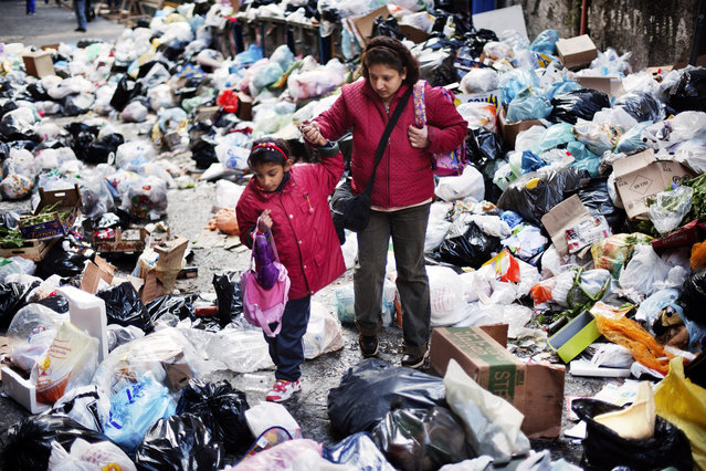 A mother walks with her child through uncollected garbage on their way back from school in the historic Spanish district of Naples on November 22, 2010. (Photo by Roberto Salomone/AFP Photo)