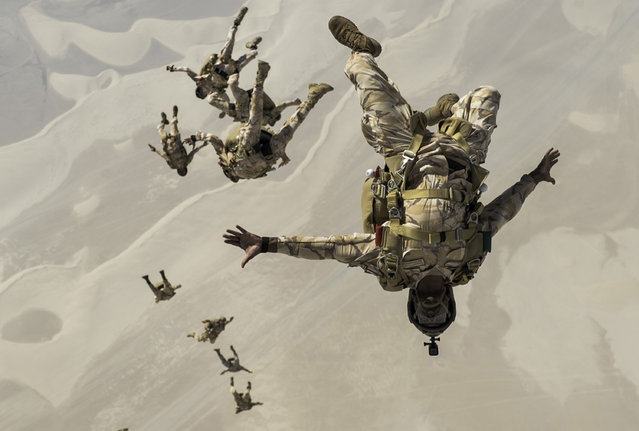 In this August 21, 2017 photo released by the U.S. Defense Department, Qatari special operations personnel conduct a military free-fall Friendship Jump over Qatar. The U.S. military has halted some exercises with its Gulf Arab allies over the ongoing diplomatic crisis targeting Qatar,  trying to use its influence to end the monthslong dispute, authorities told The Associated Press on Friday, October 6, 2017. (Photo by Staff Sgt. Trevor T. McBride/ U.S. Air Force via AP Photo)