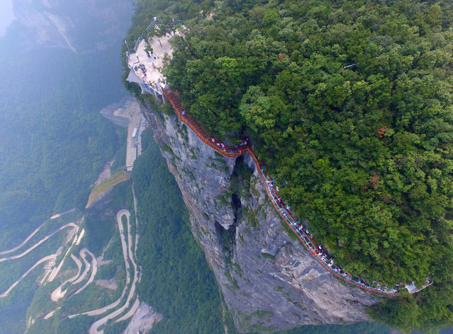 Aerial view of tourists walking on the 100-meter-long and 1.6-meter-wide glass skywalk clung the cliff of Tianmen Mountain (or Tianmenshan Mountain) in Zhangjiajie National Forest Park on August 1, 2016 in Zhangjiajie, Hunan Province of China. (Photo by  Imaginechina/Rex Features/Shutterstock)