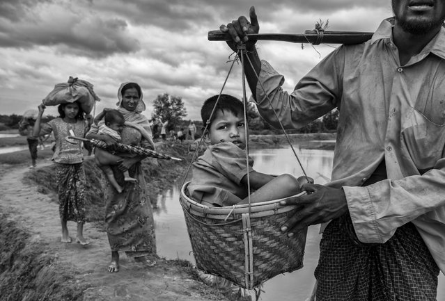 A Rohingya refugee boy is carried in a basket by a relative after crossing the border on the Bangladesh side of the Naf River while fleeing Myanmar, on September 24, 2017 in Cox's Bazar, Bangladesh. (Photo by Kevin Frayer/Getty Images)