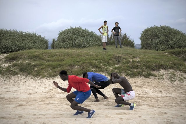 A group of friends exercise together at a beach in Marseille, southern France, Saturday, May 16, 2020. Beaches in Marseille have become partially accessible since the lifting of lockdown measures meant to prevent the spread of coronavirus. (Photo by Daniel Cole/AP Photo)