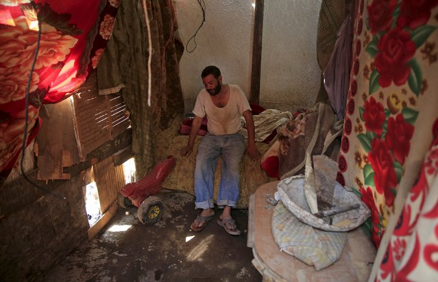 42-year-old Anwer Mostafa sits in his home in the Eshash el-Sudan slum in the Dokki neighbourhood of Giza, south of Cairo, Egypt September 2, 2015. (Photo by Amr Abdallah Dalsh/Reuters)