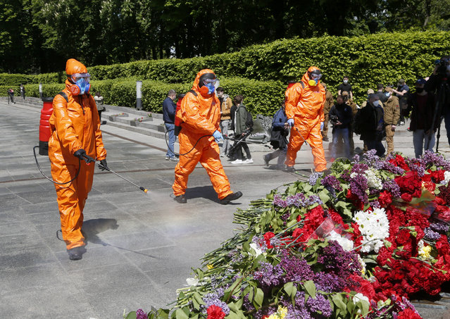 Municipal workers in special suits to protect against coronavirus disinfect an area around the monument to the Unknown Soldier in flowers at a memorial to World War II veterans in a memorial park in Kyiv, Ukraine, Saturday, May 9, 2020 on the 75th anniversary of the end of World War II. Ukraine marks the 75th anniversary of the end of World War II in Europe at a time of coronavirus lockdown and loneliness spent in search of memories both bitter and sweet. (Photo by Efrem Lukatsky/AP Photo)