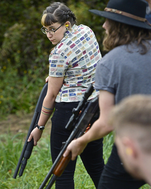 In this October. 8, 2017, photo, Zora Gussow, left, waits with a shotgun for a clay target to be thrown during a training session of the Trigger Warning Queer & Trans Gun Club in Victor, N.Y. (Photo by Adrian Kraus/AP Photo)