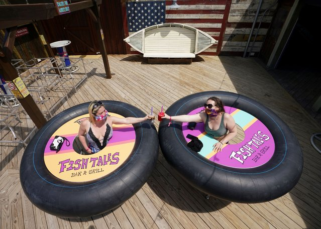 "Tracy Sandridge and Julie Brown of Baltimore pose with inner tubes on wheels dubbed ""bumper tables"" designed to ensure the coronavirus disease (COVID-19) social distancing when Fish Tales Bar & Grill eventually reopens in Ocean City, Maryland, U.S., May 23, 2020. (Photo by Kevin Lamarque/Reuters)"
