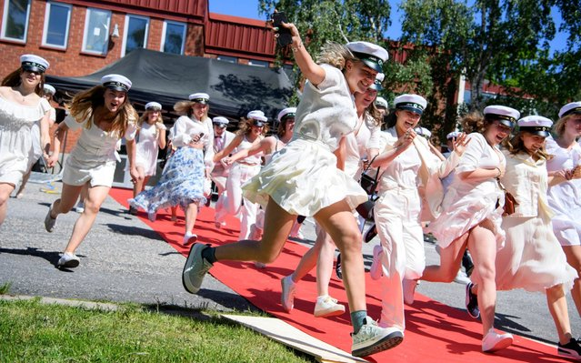 Students run out of their school celebrating their high school graduation at Nacka Gymnasium following the spread of the corona virus disease (COVID-19) in Stockholm, Sweden, June 3, 2020. (Photo by Jessica Gow/TT News Agency via Reuters)