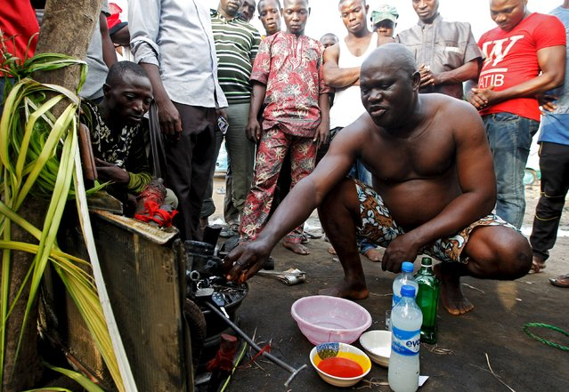 Chief priest, Gbenga Saala prays with a kolanut for one of the worshippers of the iron god Ogun during an annual prayer and sacrifice celebration in Abuja, Nigeria, June 23, 2015. Every year worshippers offer a dog as sacrifice to Ogun, a traditional Nigerian deity, in hope of an auspicious year ahead. (Photo by Afolabi Sotunde/Reuters)