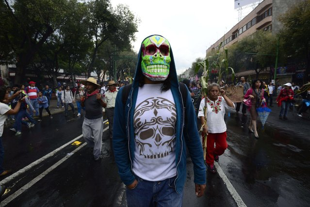A masked student takes part in a demonstration to commemorate the massacre of Tlatelolco, in Mexico City, on October 2, 2014. Mexico commemorates the 46th anniversary of a deadly clampdown on student protestors, with the details of the massacre still unclear, the perpetrators untried, and impunity as widespread as ever. According to official figures, Mexican security forces killed 44 protesting students, though social organizations claim there were over 300 people killed. Students also demand authorities to find 43 students missing since a deadly police shooting last weekend in Guerrero state. (Photo by Alfredo Estrella/AFP Photo)
