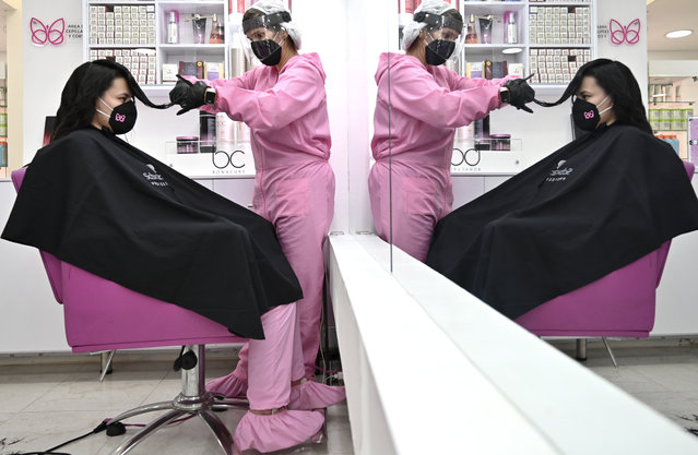 A stylist and a customer wear protective equipment as a preventive measure against the COVID-19 coronavirus, at a beauty salon in Bogota on June 23, 2020. (Photo by Raul Arboleda/AFP Photo)