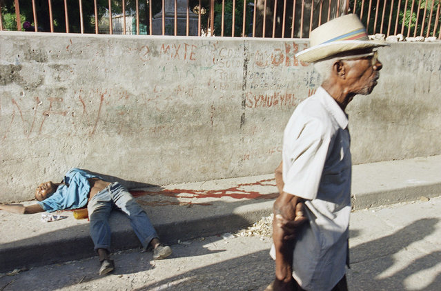 A Haitian walks by a murdered man on the sidewalk near the Catholic Cathedral, Sunday, September 18, 1994 in Port-au-Prince, Haiti. An American invasion of Haiti was averted Sunday night in the most dramatic fashion as President Clinton's negotiators reached an 11th-hour compromise with Army commander Raoul Cedras. Clinton said Haiti's military rulers would leave power by October 15. (Photo by Bebeto Matthews/AP Photo)