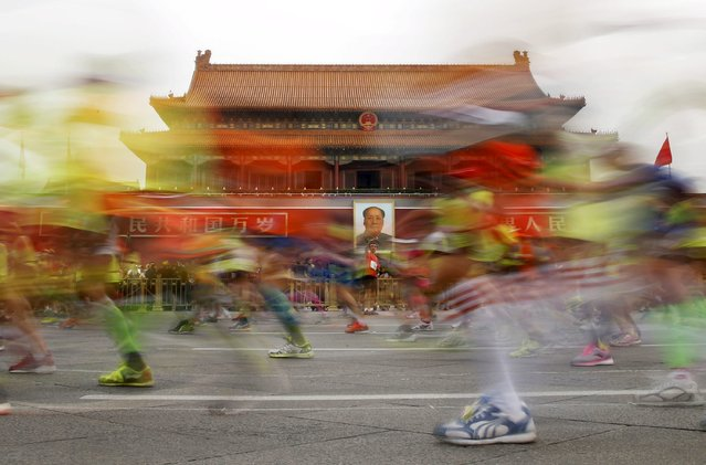 Participants run past the Tiananmen gate, with a portrait of China's late leader Mao Zedong hanging on it, during the Beijing International Marathon in Beijing, China, September 20, 2015. About 30,000 runners participated in the annual running event. (Photo by Kim Kyung-Hoon/Reuters)