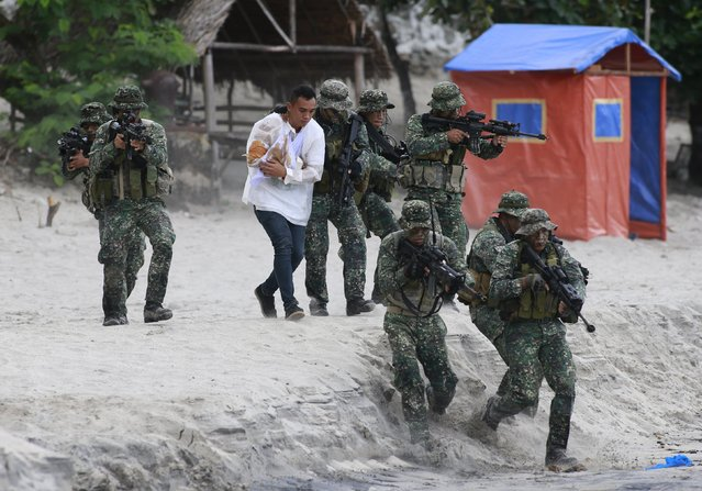 Members of the Philippine Marines rescue a hostage from mock rebels during the Fleet-Marine Amphibious Exercise at the marine headquarter in Ternate, cavite city, south of Manila September 24, 2015. (Photo by Romeo Ranoco/Reuters)