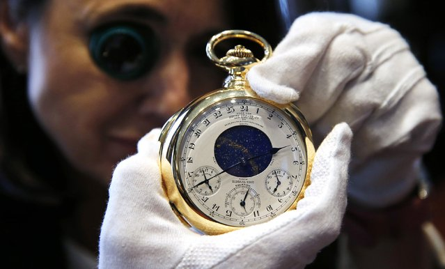 """Chairman of Sotheby's Watch Division Daryn Schnipper poses with """"The Henry Graves Supercomplication"""" handmade watch by Patek Philippe which was completed in 1932 at Sotheby's auction house in London October 21, 2014. This masterpiece of horology is estimated to sell in excess of close to 10 million pounds when it is auctioned on November 11 in Geneva. (Photo by Suzanne Plunkett/Reuters)"""