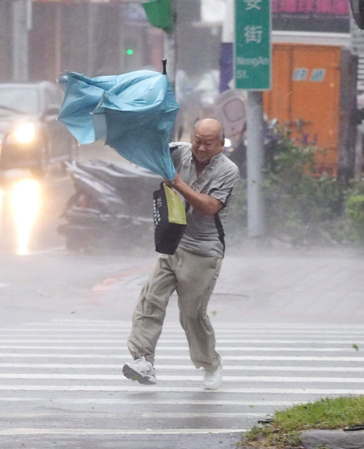 A man struggles with his umbrella as he crosses a street in Taipei, Taiwan, 28 September 2015 as Typhoon Dujuan slams Taiwan. Dujuan, called a strong tyhoon by the Central Weather Bureau, landed on Taiwan's east coast Monday afternoon, bringing strong wind and heavy rain and disrupting land and air traffic. Dujuan will pass Taiwan Monday night on its way to China. (Photo by David Chang/EPA)