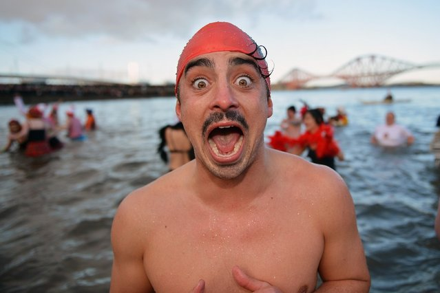 A man reacts as he joined by over 1,000 New Year swimmers, many in costume, braved freezing conditions in the River Forth in front of the Forth Rail Bridge during the annual Loony Dook Swim on January 1, 2013 in South Queensferry, Scotland. Thousands of people gathered last night to see in the New Year at Hogmanay celebrations in towns and cities across Scotland.  (Photo by Jeff J. Mitchell)