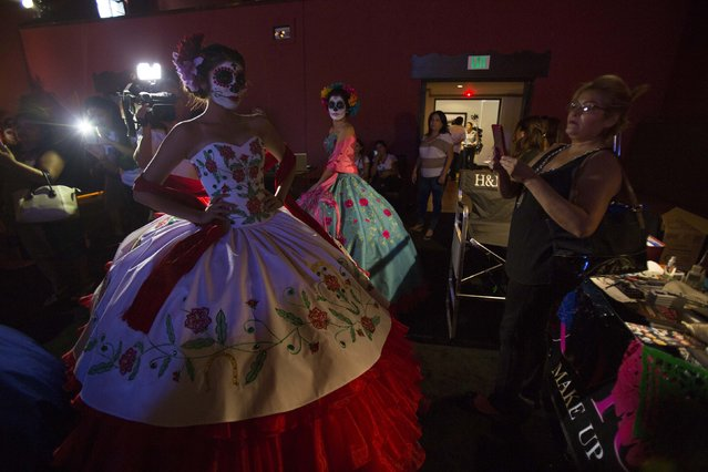 Models are pictured during a Quinceanera Magazine Catrina fashion show at a press reception ahead of the 15th annual Dia de los Muertos, or Day of the Dead, festival at Hollywood Forever Cemetery in Los Angeles, California October 24, 2014. The Day of the Dead festival has its origins in a pre-Hispanic Aztec belief that the dead return to Earth one day each year to visit their loved ones. The festival will be held on November 1. (Photo by Mario Anzuoni/Reuters)