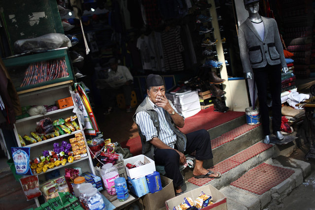 A Nepalese man waits for customers at his shop in Kathmandu, Nepal, Thursday, October 1, 2015. Indian trucks carrying food and fuel began trickling into Nepal on Wednesday, a welcomed development for a nation grappling with shortages caused by a blockade during protests against the country's new constitution. Nepal has restricted the movement of vehicles due to the fuel shortages, with cars permitted to run only on alternate days. (Photo by Niranjan Shrestha/AP Photo)