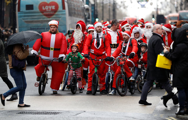 Santa's on BMX cycles take part in a charity ride along Oxford street in London, England on December 16, 2017. (Photo by Peter Nicholls/Reuters)