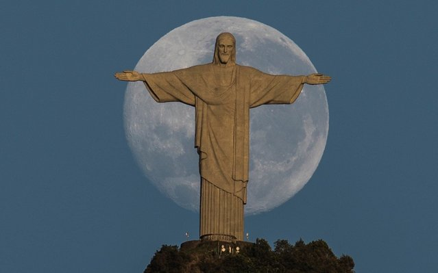 A full moon is seen just right behind the Christ the Redeemer monument in Rio de Janiero, Brazil, 05 August 2020. (Photo by Antonio Lacerda/EPA/EFE/Rex Features/Shutterstock)