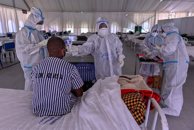 Medical staff in personal protective equipment (PPE) review a patient during rounds at a mass isolation facility for COVID-19 (novel coronavirus) patients on August 3, 2020 at Kenya's eastern town of Machakos. (Photo by Tony Karumba/AFP Photo)