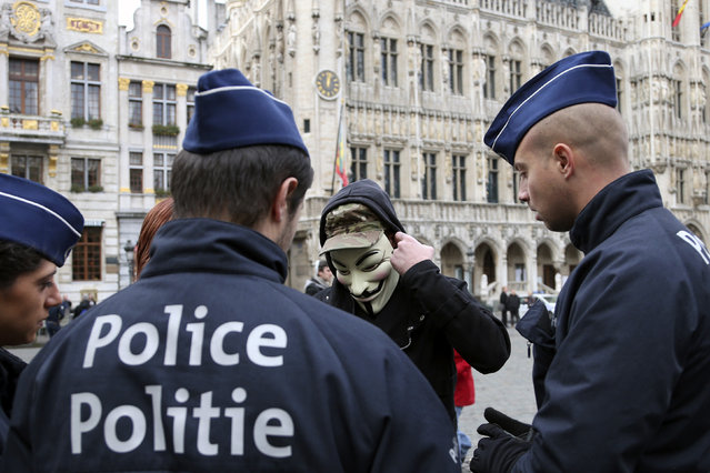 Police officers check the identity papers of a protester wearing a Guy Fawkes mask during a protest on Grand Place in Brussels November 5, 2014. (Photo by Francois Lenoir/Reuters)