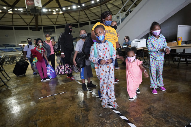 Victoria Nelson with her children Autum Nelson, 2, Shawn Nelson, 7, and Asia Nelson, 6, line up to board a bus to evacuate Lake Charles, La., Wednesday, August 26, 2020, ahead of Hurricane Laura. (Photo by Gerald Herbert/AP Photo)