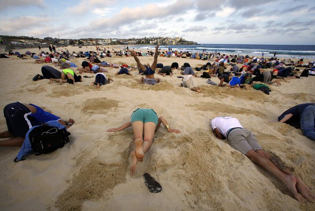 "A group of around 400 demonstrators participate in a protest by burying their heads in the sand at Sydney's Bondi Beach November 13, 2014. Hundreds of protesters participated in the event, held ahead of Saturday's G20 summit in Brisbane, which was being promoted as a message to Australian Prime Minister Tony Abbott's government that, ""You have your head in the sand on climate change"". (Photo by David Gray/Reuters)"