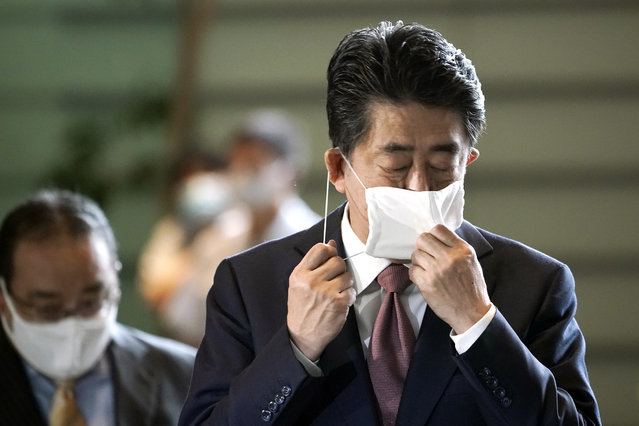 Japan's outgoing Prime Minister Shinzo Abe takes off his face mask as he arrives at the prime minister's office for a cabniet meeting Wednesday, September 16, 2020, in Tokyo. Abe and his Cabinet resigned, clearing the way for his successor Yoshihide Suga to take over after parliamentary confirmation later in the day. (Photo by Eugene Hoshiko/AP Photo)