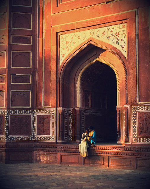 """""""Dusk at the Taj Mahal, and away from the tourists I noticed two friends chatting. I was drawn to their beautiful coloured clothing against the architecture"""". (Photo by Stella Chidzik/The Guardian)"""