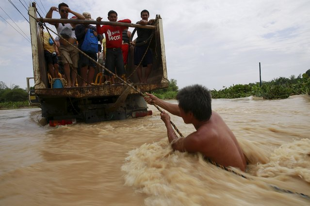 A man holds on a rope as he tries to board a truck while crossing floodwaters brought by typhoon Koppu that battered Candaba town, Pampanga province, north of Manila October 20, 2015. (Photo by Romeo Ranoco/Reuters)