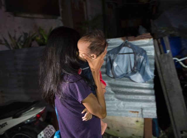 A resident carrying her child mourns after learning a relative and a suspected drug pusher was killed during a drug buy-bust operation by police along a rail line in Caloocan City suburban Manila on early September 30, 2016. (Photo by Ted Aljibe/AFP Photo)