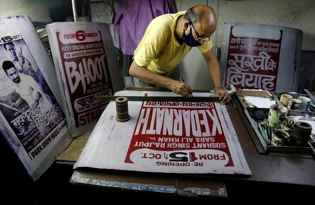 A graphic designer paints a Bollywood movie poster on an aluminium sheet inside a workshop ahead of the reopening of cinema halls, amidst the outbreak of the coronavirus disease (COVID-19), in Kolkata, India, October 13, 2020. (Photo by Rupak De Chowdhuri/Reuters)