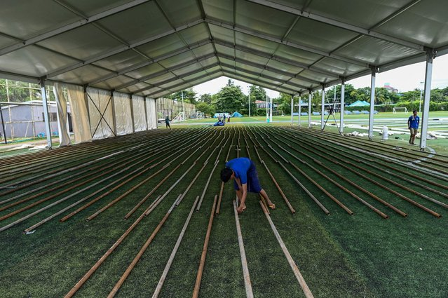 A worker builds new temporary shelters for COVID-19 related cases on a football pitch in Yangon on September 13, 2020. Nearly all of Myanmar, including the capital Naypyidaw, Yangon and northwestern Rakhine state, are now all under lockdown due to a surge in cases of the COVID-19 coronavirus as calls grow for a postponement to national elections in November. (Photo by Ye Aung Thu/AFP Photo)