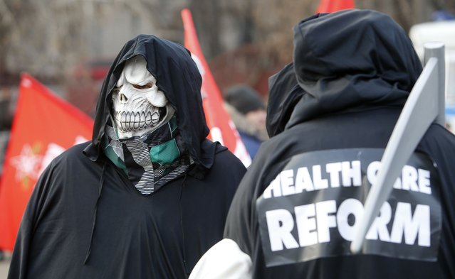 An activist wears a skull mask during a protest in support of Russian doctors and patients against reforms to the healthcare system in Moscow November 30, 2014. Protesters opposed low wages of Moscow's doctors and the plan to optimize the healthcare system, according to local media. (Photo by Sergei Karpukhin/Reuters)