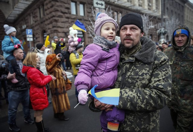 "A serviceman of ""Kiev 12"" military defence battalion holds his daughter as he march on Khreshchatyk street during a welcoming ceremony in Ukrainian capital Kiev December 6, 2014. (Photo by Gleb Garanich/Reuters)"