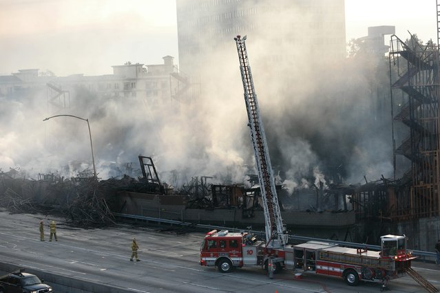 Fire crews work on smoldering hot spots of a large fire that consumed an apartment building that was under construction in Los Angeles, California December 8, 2014. The blaze in downtown Los Angeles early on Monday shut down two major freeways, the Los Angeles Fire Department and California Highway Patrol said. (Photo by Jonathan Alcorn/Reuters)