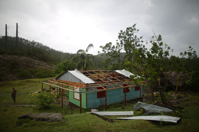 Farmer Nicolas Maturel, 27, stands next to his damaged house after the passage of Hurricane Matthew in Carbonera, Cuba, October 5, 2016. (Photo by Alexandre Meneghini/Reuters)