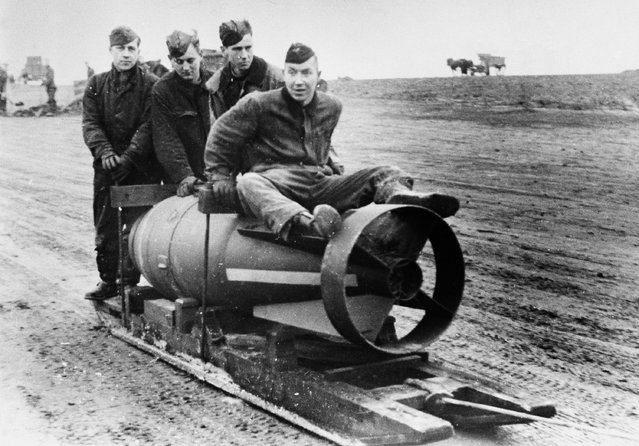 A heavy German bomb is dragged to a bombing plane at an airport in France on January 31, 1941 for use in an air raid on England. (Photo by AP Photo)