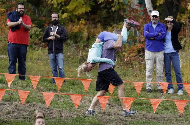 Henry Tabur carries Kim Joyce, both of Pembroke, Mass., while racing in the North American Wife Carrying Championship, Saturday, October 8, 2016, at the Sunday River Ski Resort in Newry, Maine. Carrying your wife over the threshold means good luck in your new marriage. Carrying your wife over the threshold of an obstacle course featuring log hurdles, sand traps and water hazards means beer and cash prizes. A husband and wife from Maine are this year's winners of the North American Wife Carrying Championship held Saturday in Newry, Maine and will compete in the world championship in Finland next year. (Photo by Robert F. Bukaty/AP Photo)