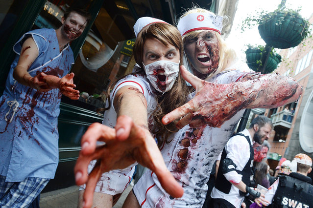 People dressed as zombies participate in a parade for World Zombie Day 2016 in London's West End, Britain on October 9, 2016. (Photo by Splash News and Pictures)