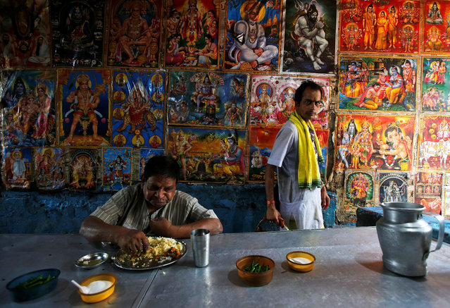 A man eats at a roadside stall as a Hindu priest walks past a wall with posters of Hindu deities at a market area in Kolkata, March 13, 2018. (Photo by Rupak De Chowdhuri/Reuters)