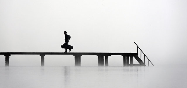 A man walks on a pier at lake Ammersee in Stegen, southern Germany, during heavy fog with temperatures around three degrees Celsius on November 10, 2020. (Photo by Christof Stache/AFP Photo)