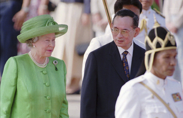 In this October 28, 1996, file photo, Thailand's King Bhumibol Adulyadej, second right, walks with Britain's Queen Elizabeth II after her arrival at Bangkok's military airport.  (Photo by Richard Vogel/AP Photo)