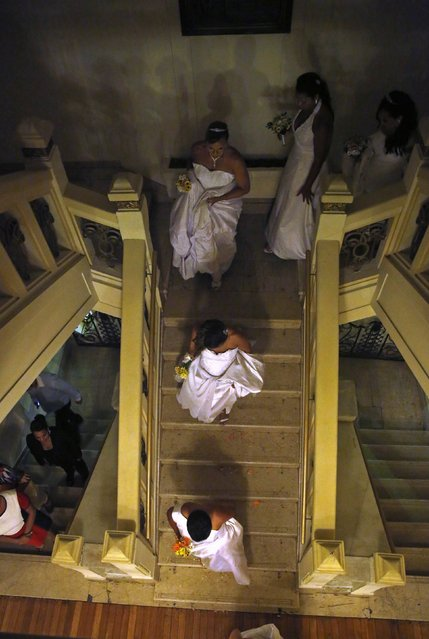 Brides descend the stairs for their group wedding in Rio de Janeiro December 17, 2014. (Photo by Pilar Olivares/Reuters)